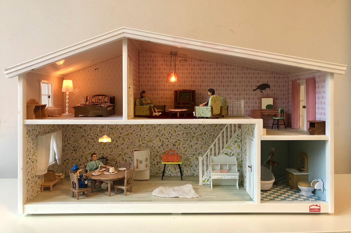 Kaksikerroksinen Lundby-nukkekoti. Yläkerrassa istuu kaksi lasta, alakerrassa isä ja poliisi.
